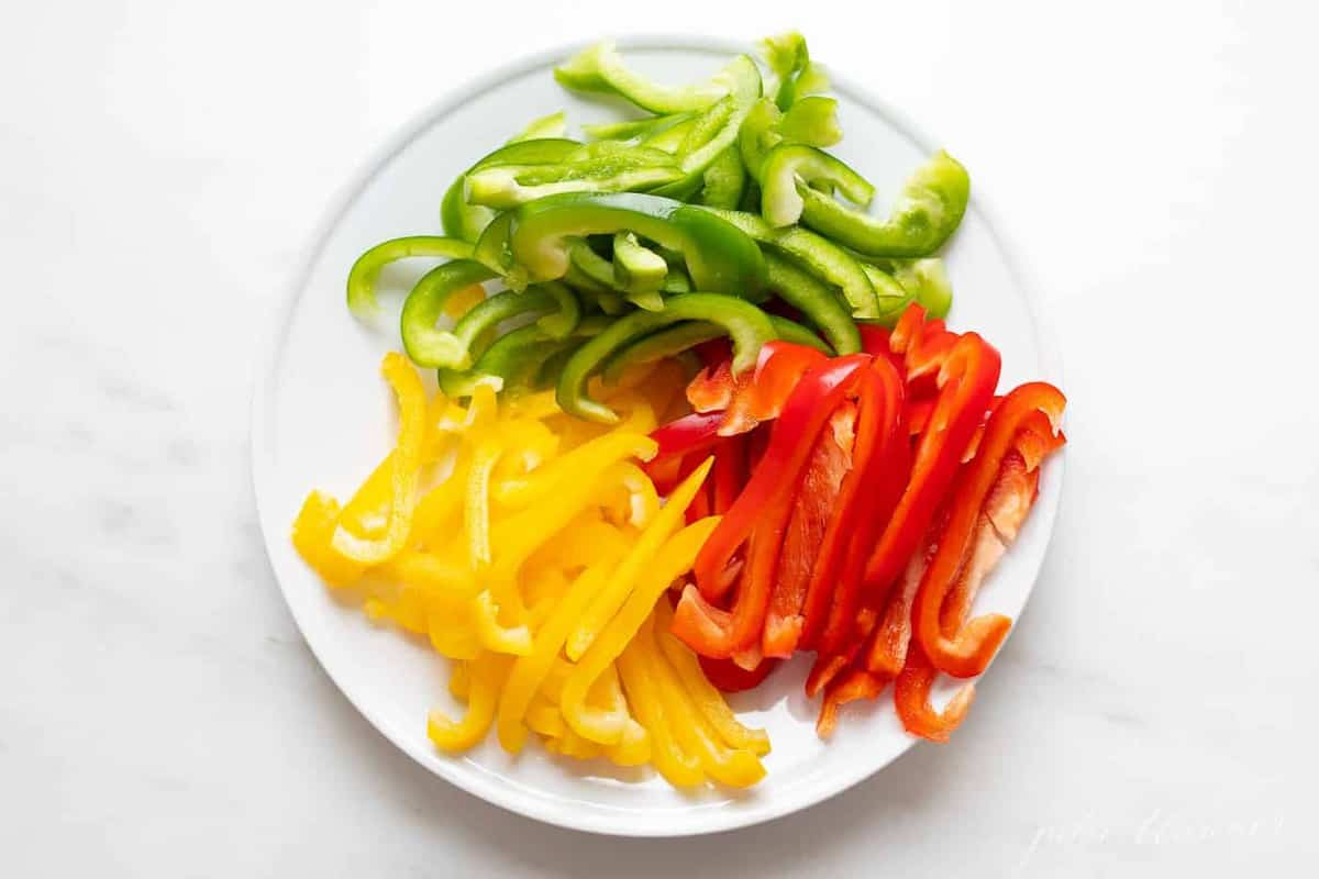 Red, green, and yellow bell peppers cut on a white plate on a white surface.