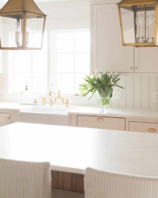 A white kitchen with a simple vase of flowers on the island.