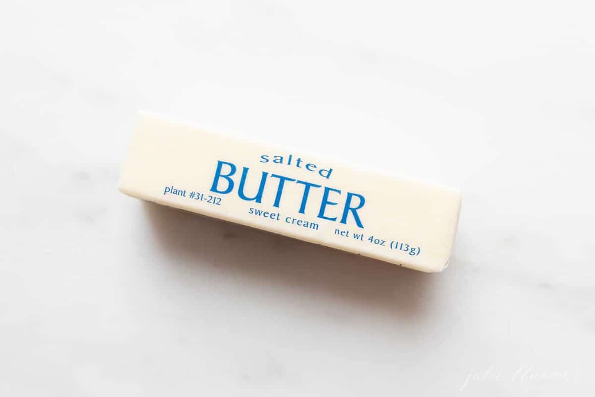 A stick of wrapped salted butter on a marble surface.