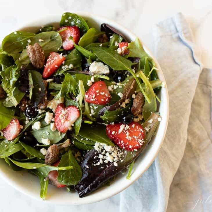 A white bowl full of a fresh spring mix salad.