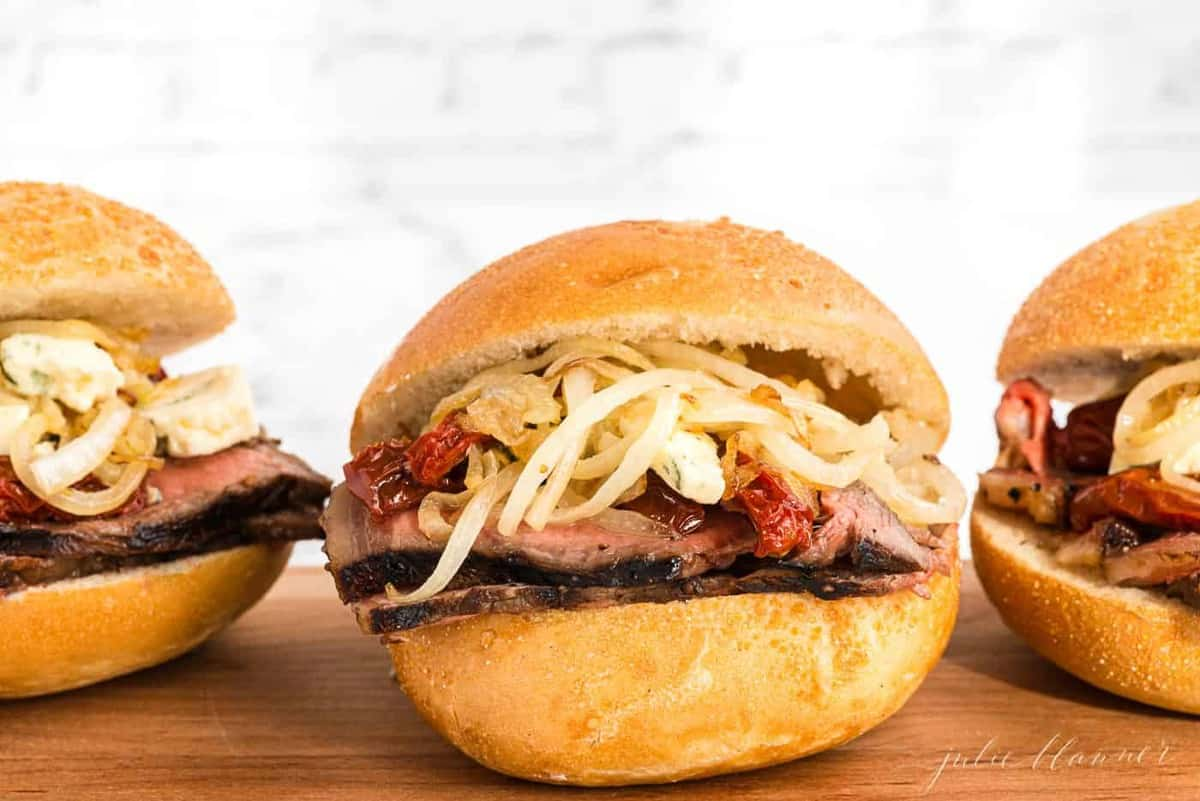 A trio of steak sandwiches stacked with ingredients on a round bun.