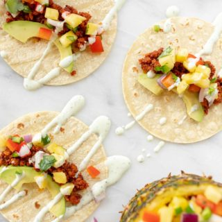 marble surface with three chorizo tacos loaded with toppings, pineapple salsa to the side.