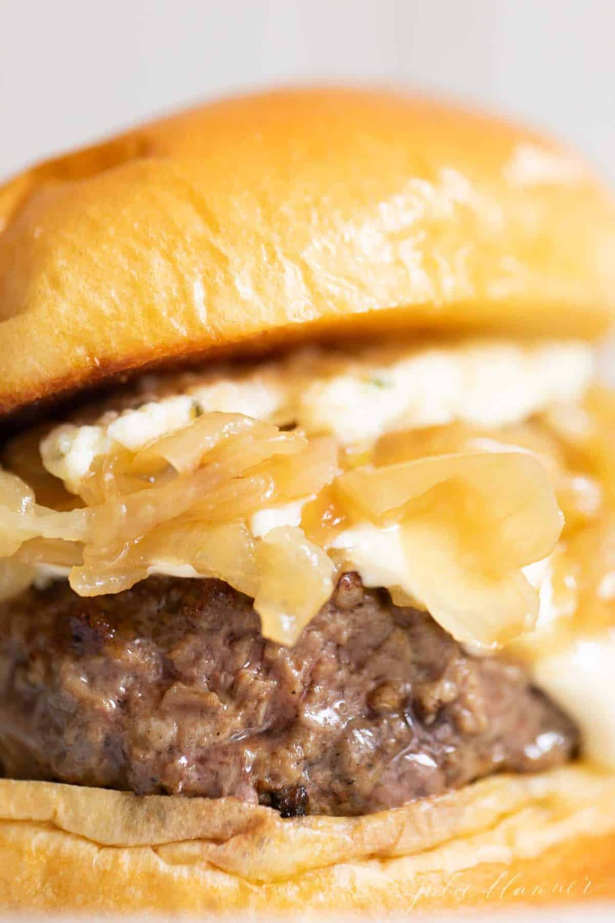 Close up of a gourmet burger with caramelized onions and boursin cheese.