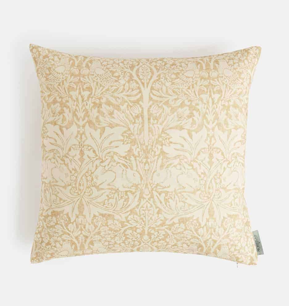 A product shot of an ivory patterned pillow cover.