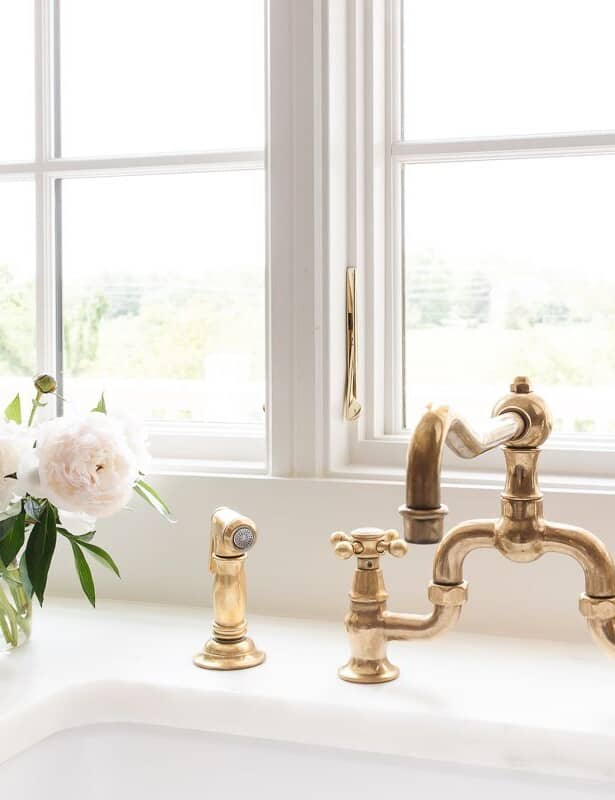 A kitchen sink with a brass faucet and a white peony flower arrangement to the side.