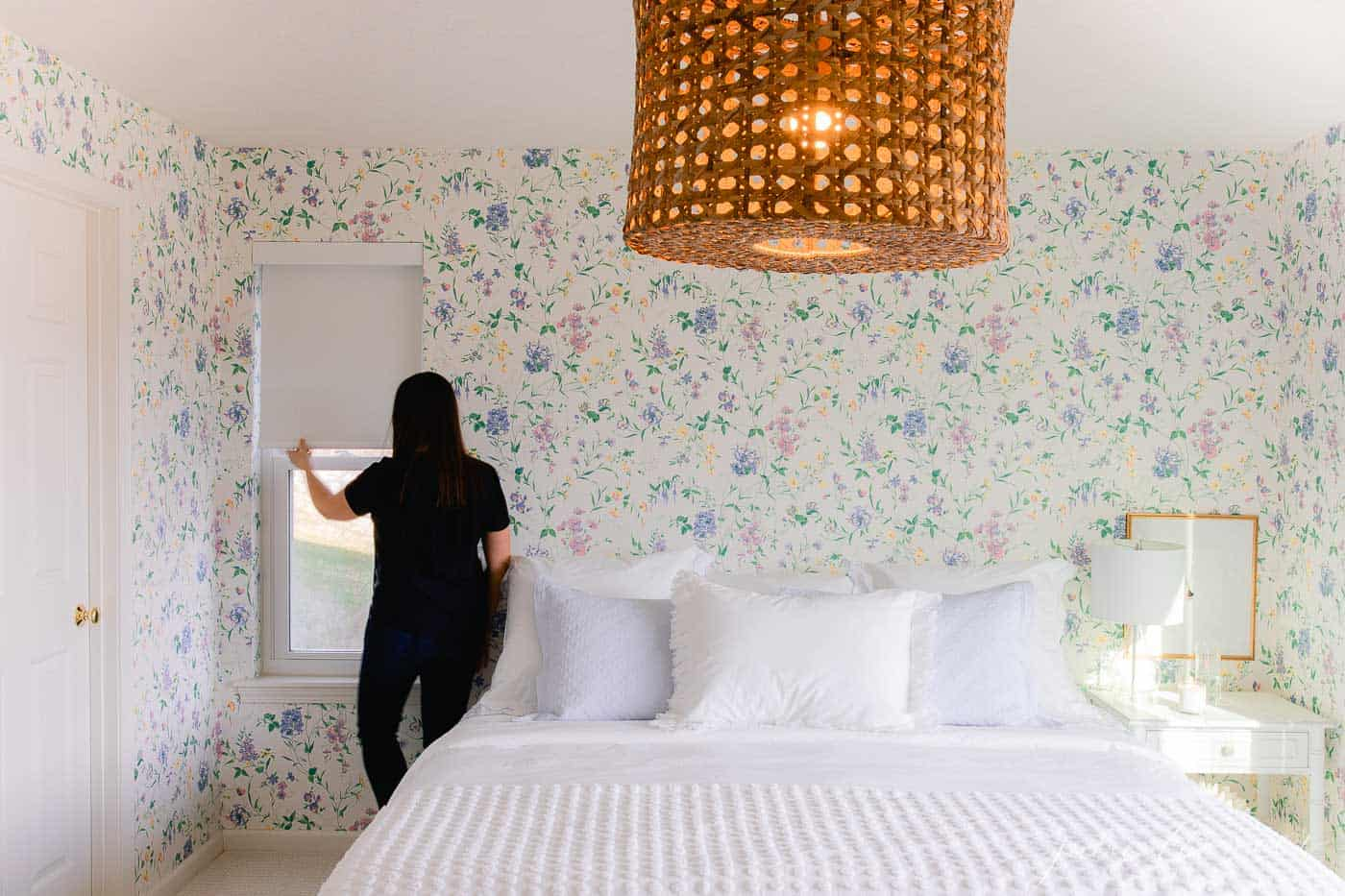 A cottage bedroom with white bedding, floral wallpaper, and a small window with a custom roller shade, woman at the window pulling shade down.