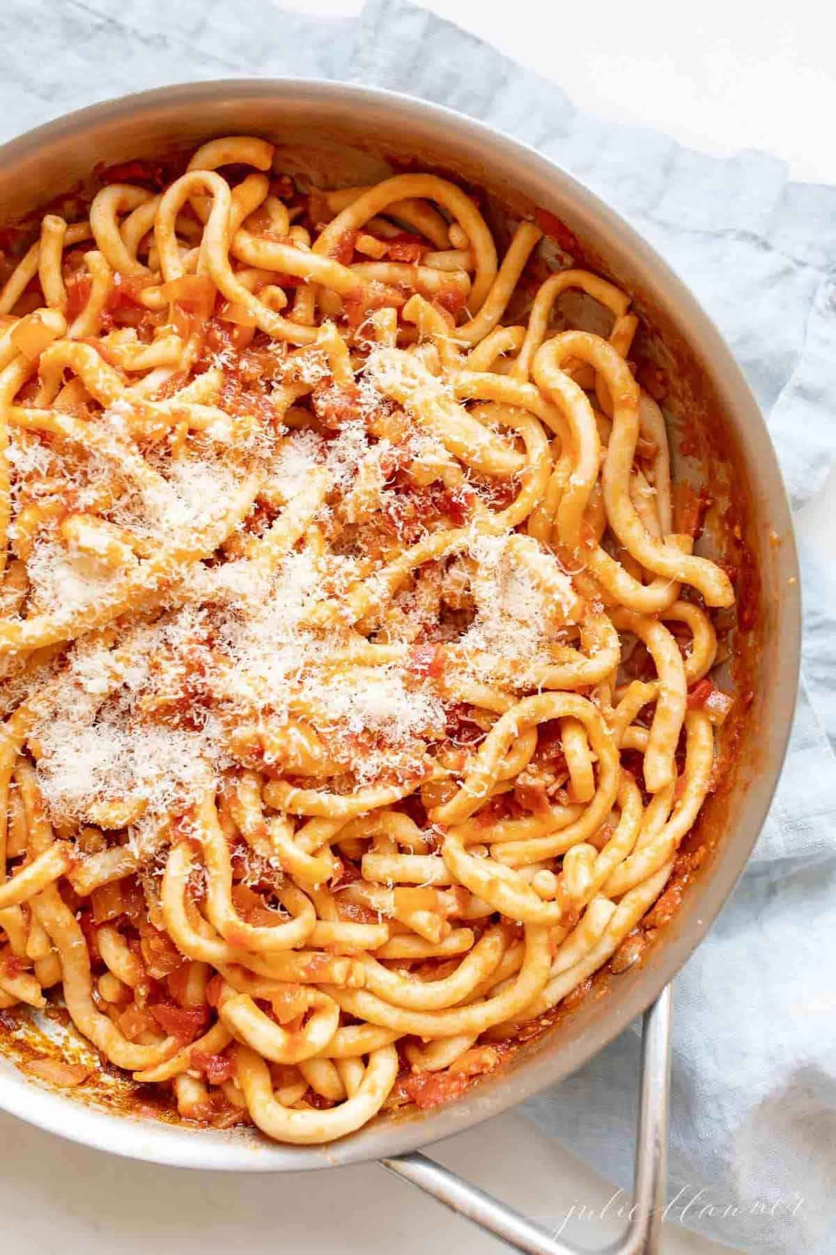 A silver pan, filled with Amatriciana pasta, topped with parmesan