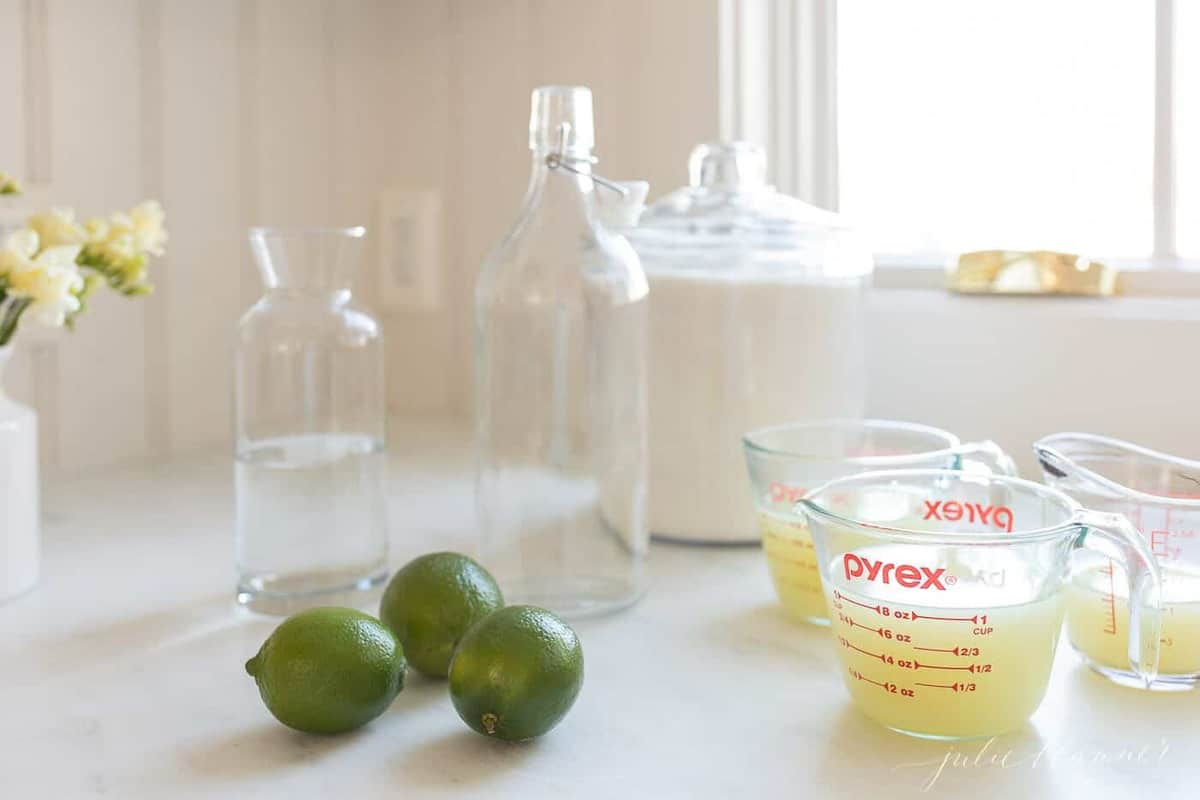 Glass bottles, limes and fresh squeezed lime juice for a homemade margarita mix.