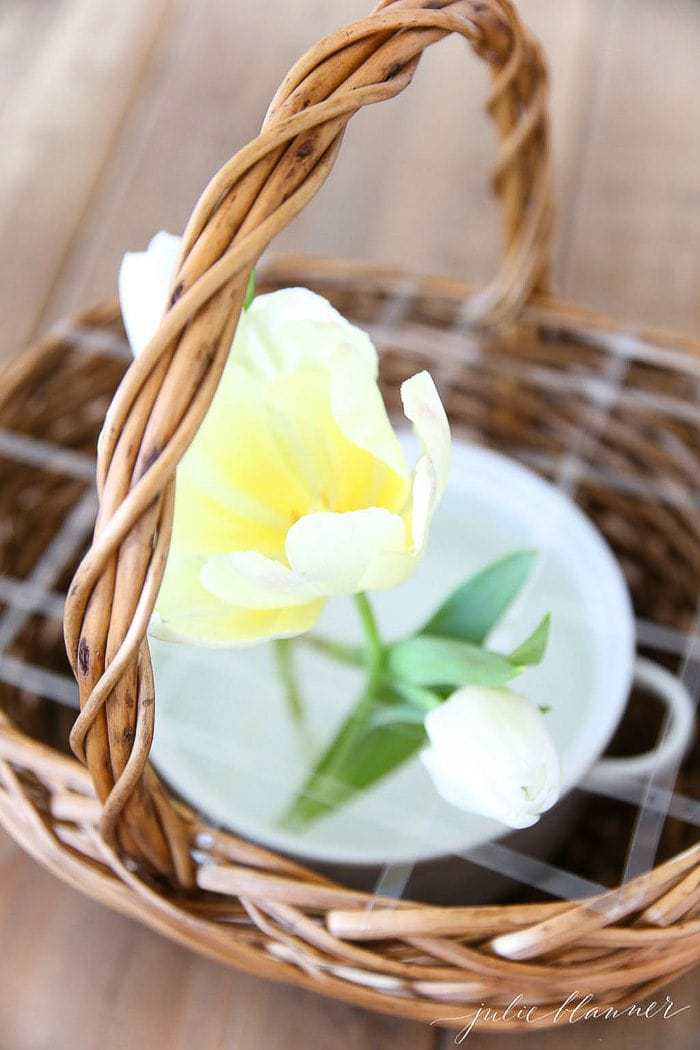 A wicker basket with a white dish inside, yellow tulips placed at the beginning of a flower basket arrangement.