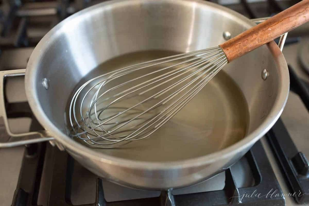 A stainless steel pan with a whisk inside, which creates simple syrup for the margarita mix.