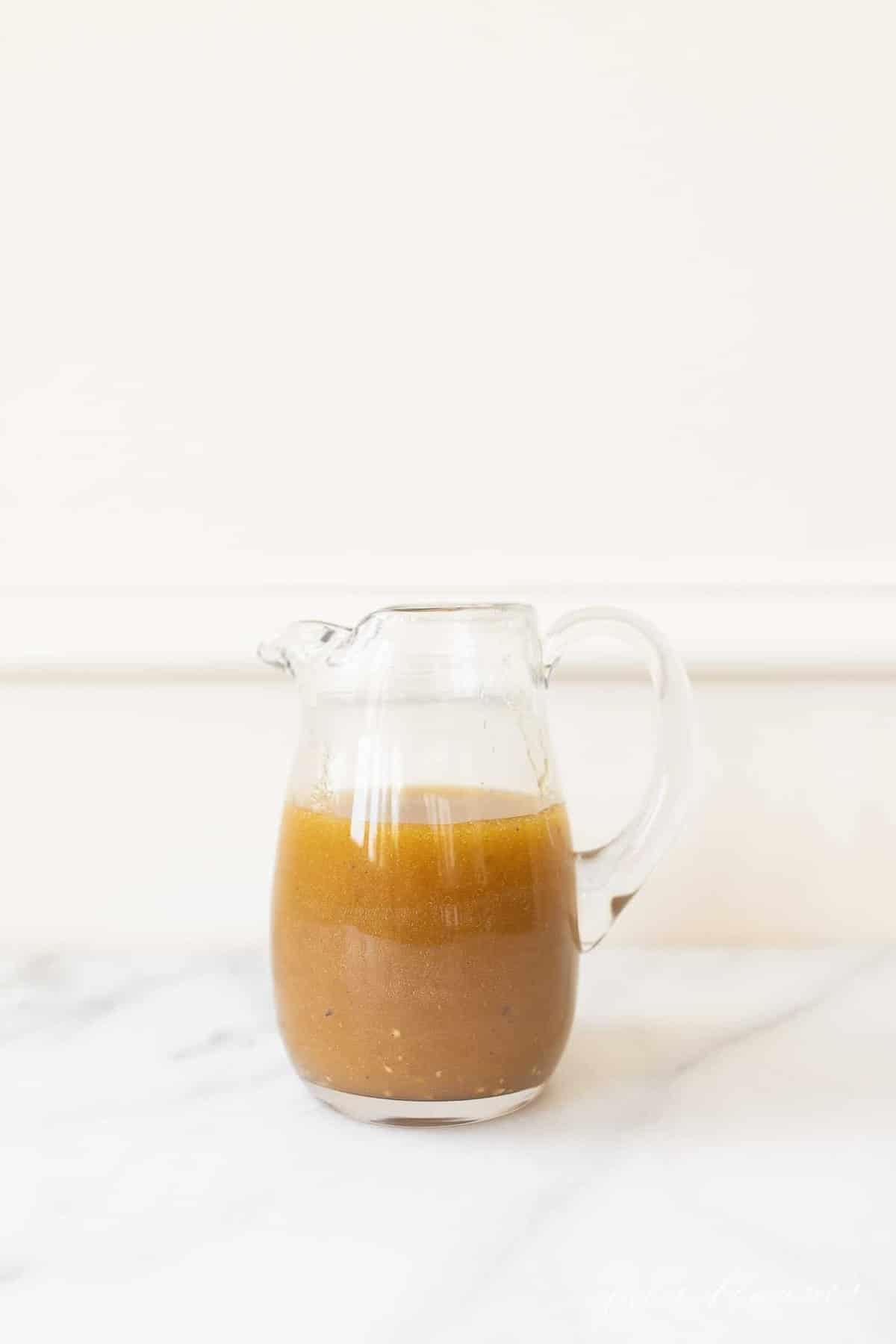 A clear glass pitcher of homemade vinaigrette dressing.