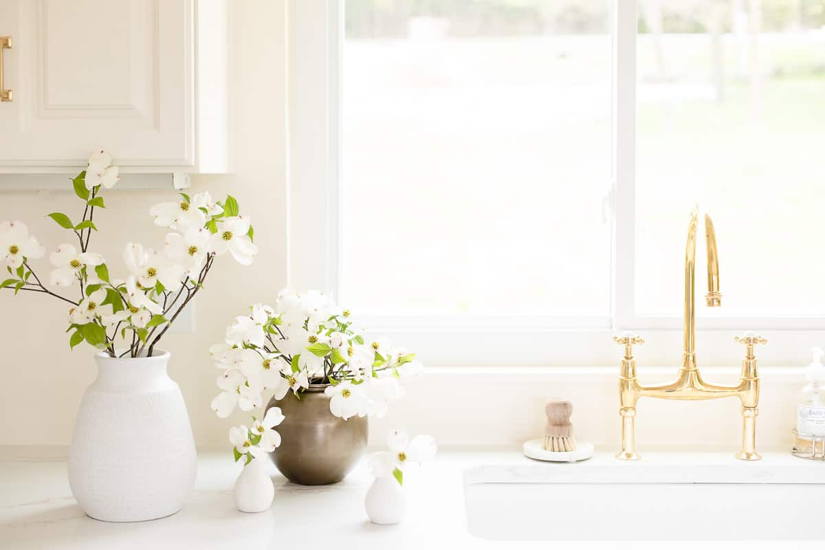 kitchen with brass faucet and flowers