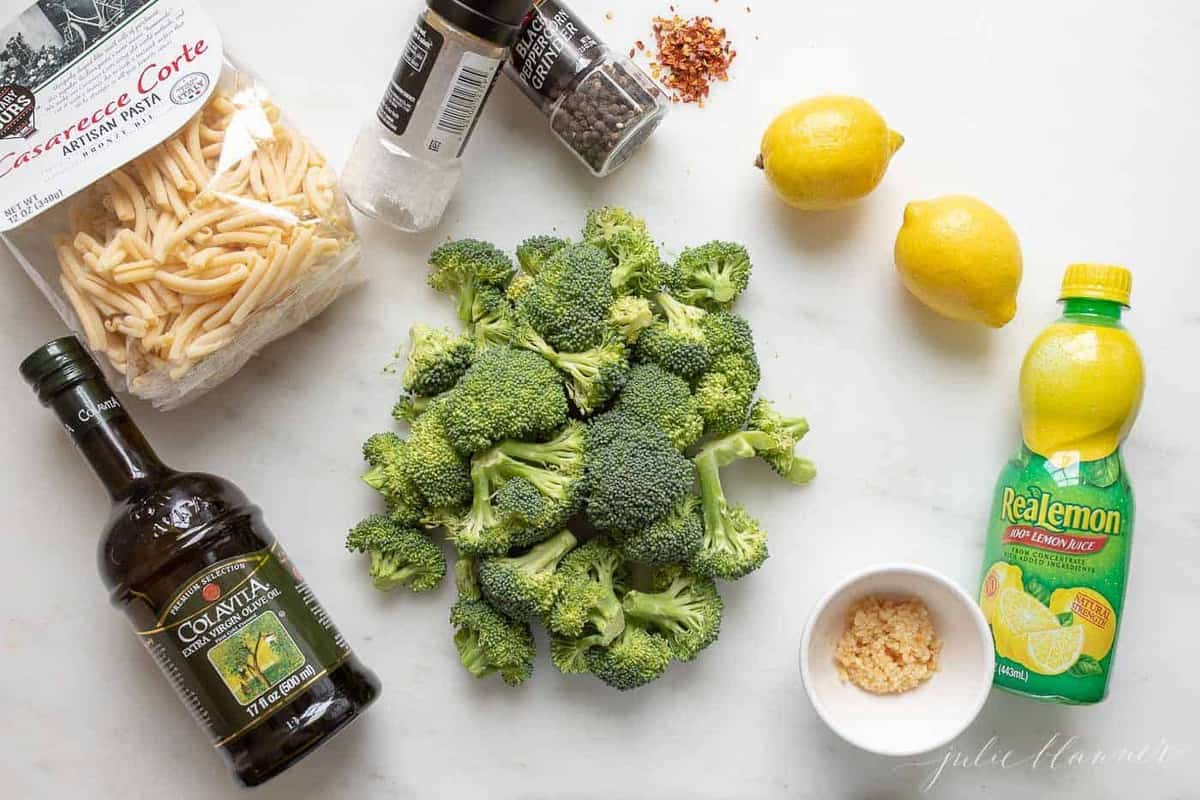 A white surface with ingredients for broccoli pasta