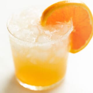 Marble surface, clear glass full of cadillac margarita garnished with orange slice.
