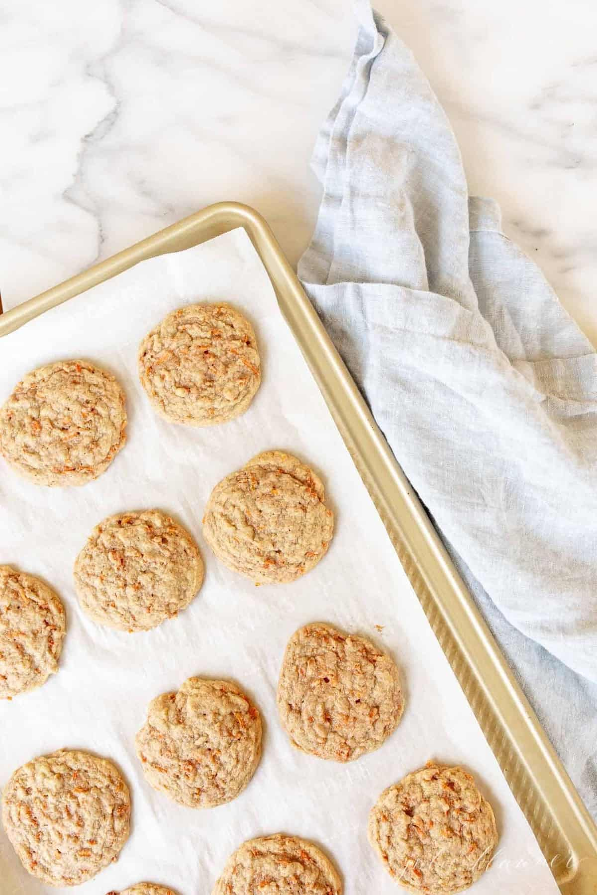 Gold baking sheet with carrot cookies.