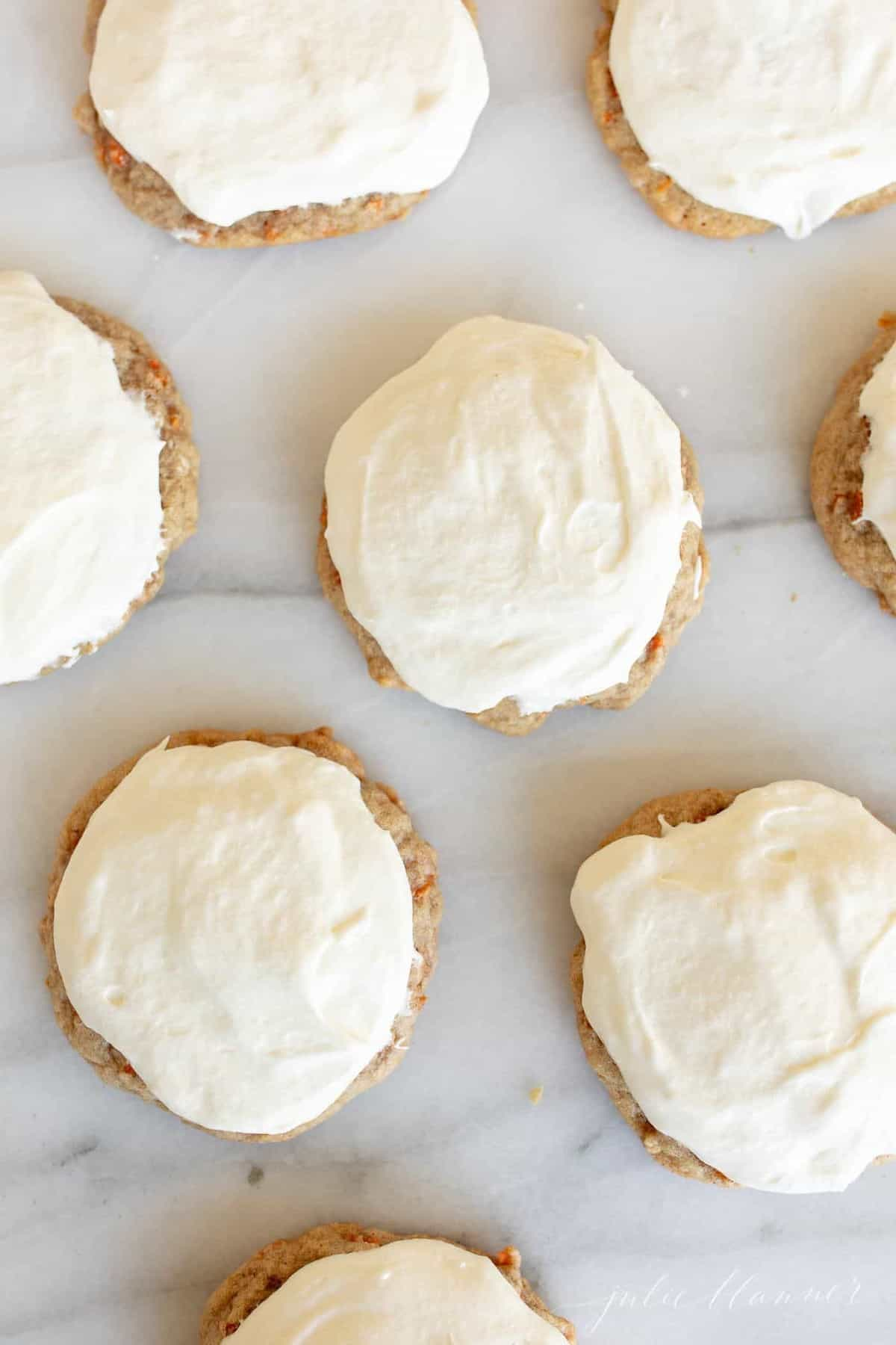 Marble surface with carrot cake cookies covered in cream cheese frosting.