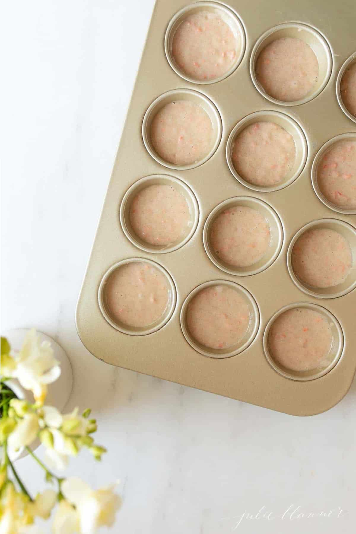 A gold muffin pan filled with carrot cake muffin batter.
