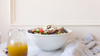 A white kitchen background with a white bowl full of salad and champagne dressing in a clear pitcher.