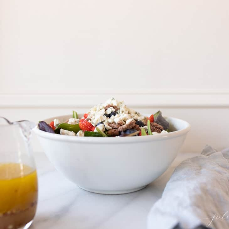 A white kitchen background with a white bowl full of salad and champagne vinaigrette in a clear pitcher.