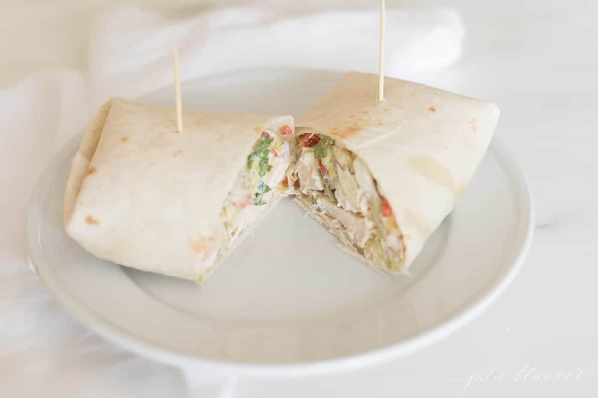 White plate with a chicken wrap, cut in half