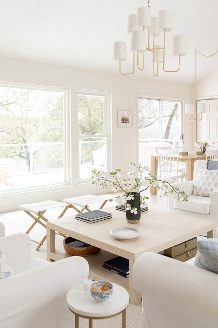 coastal modern living room with raffia coffee table and gold chandelier