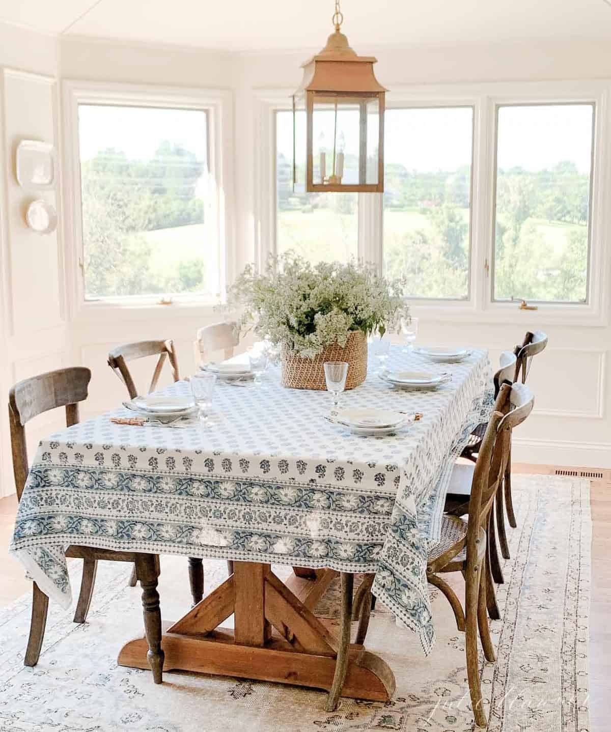 A white dining room with lots of windows, table set with blue and white Kalamkari tablecloth