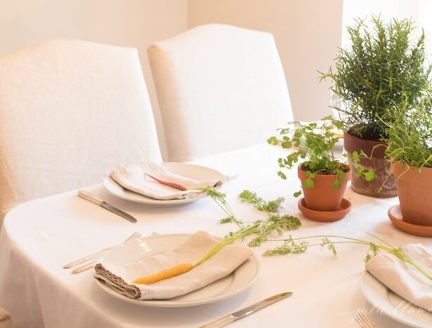 A white dining room that is set with an Easter flower centerpiece.