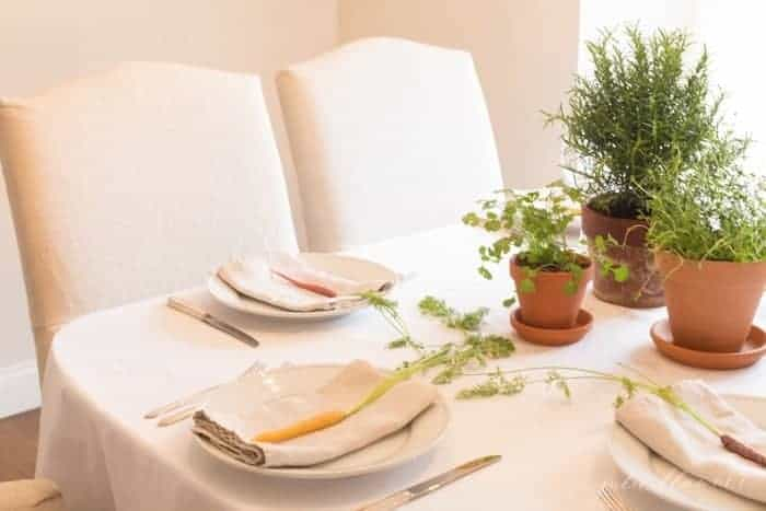 A formal dining table set with a centerpiece of potted herbs for Easter table decor.