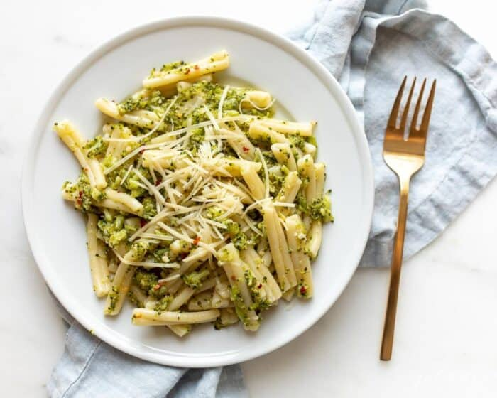 A white plate filled with broccoli pasta, blue napkin behind.