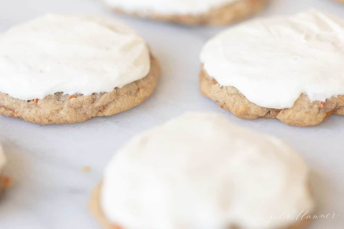 Carrot cake cookies frosted with cream cheese frosting on a marble surface.