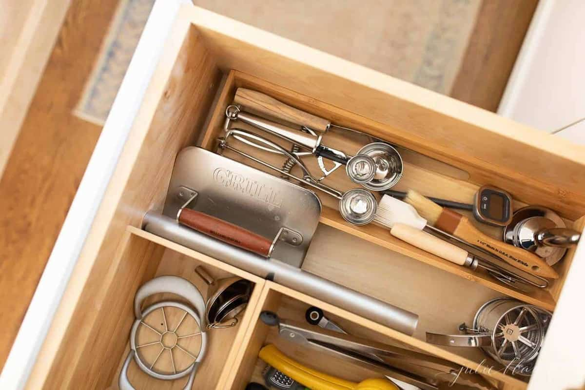Looking into a drawer full of kitchen drawer inserts with utensils.