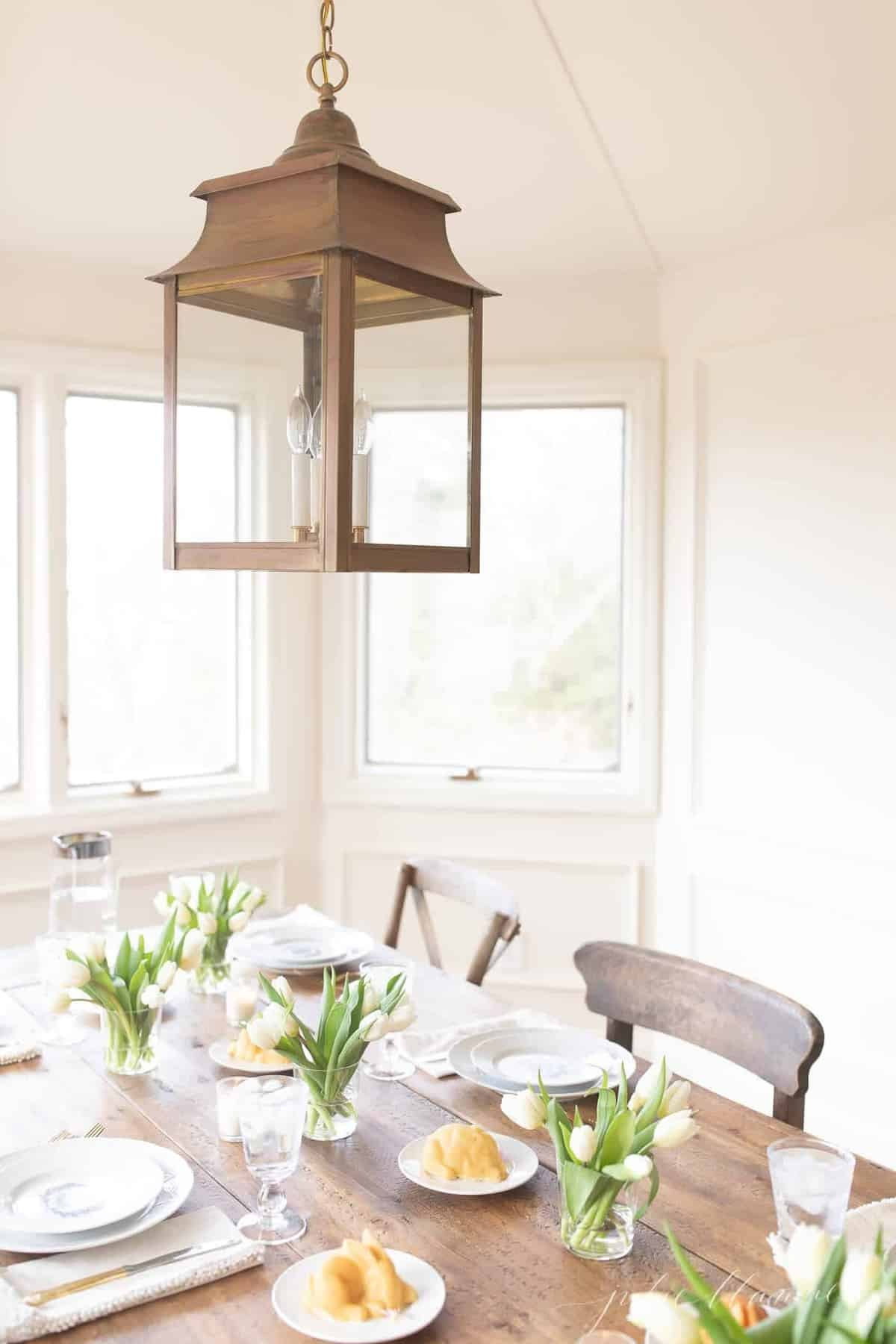 A white dining room with an Easter centerpiece of tulips in small vases
