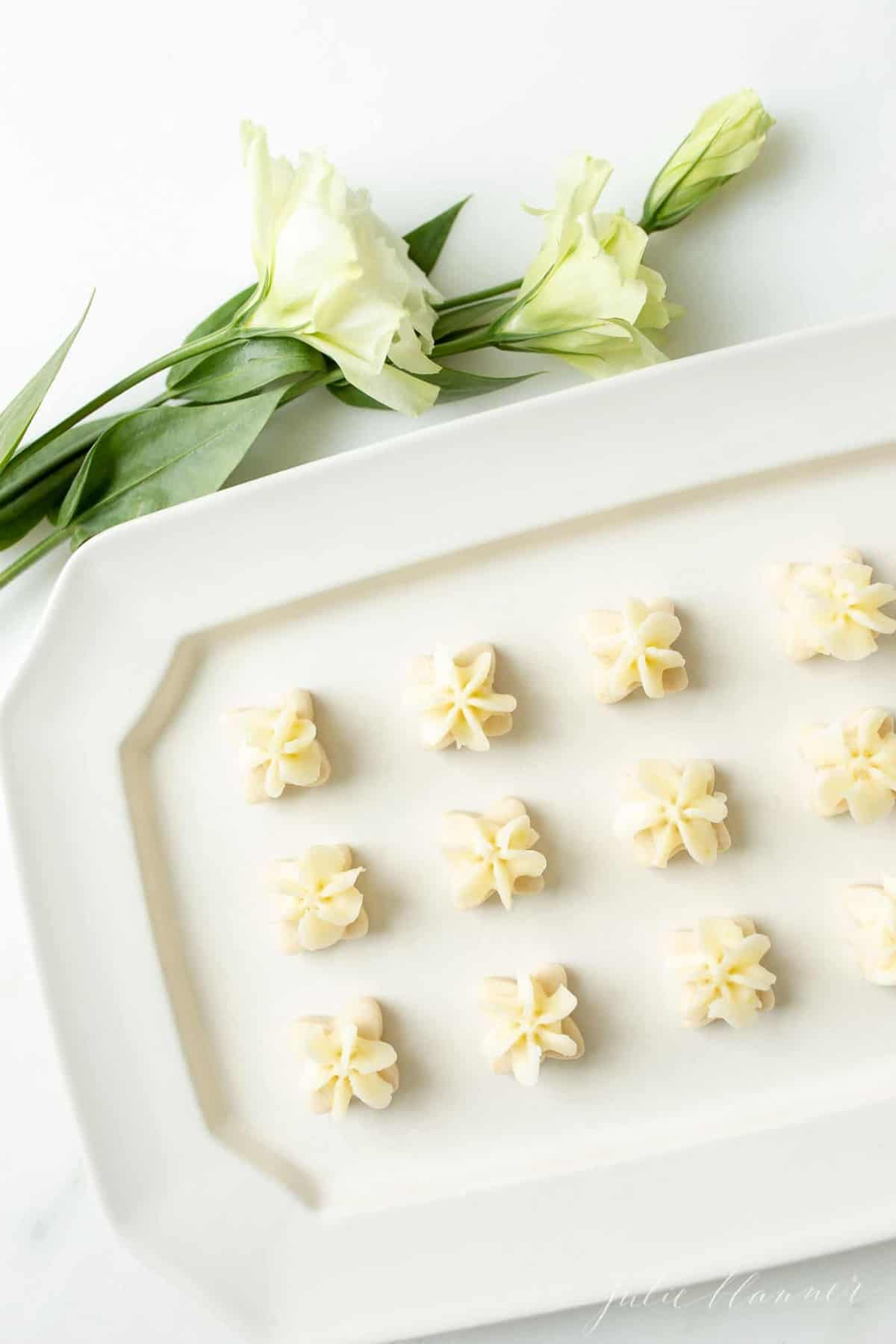 Tiny flower shaped lemon frosted cookies on a white platter, fresh flowers to the side.