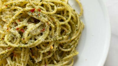 A white plate full of a pesto pasta recipe, topped in parmesan