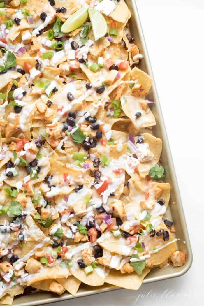 An easy weeknight dinner of sheet pan nachos on a gold pan.