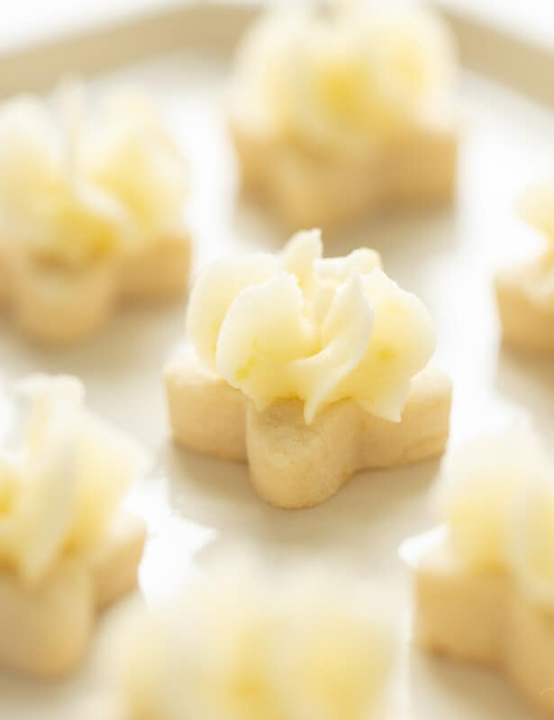 Tiny flower shaped lemon frosted cookies on a white platter.