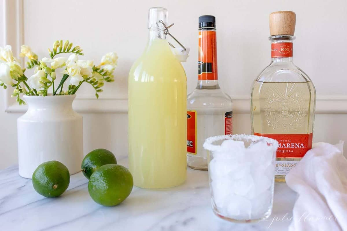 Homemade margarita mix in a glass carafe, limes, a glass, and liquor; a vase full of yellow flowers sits to the side.