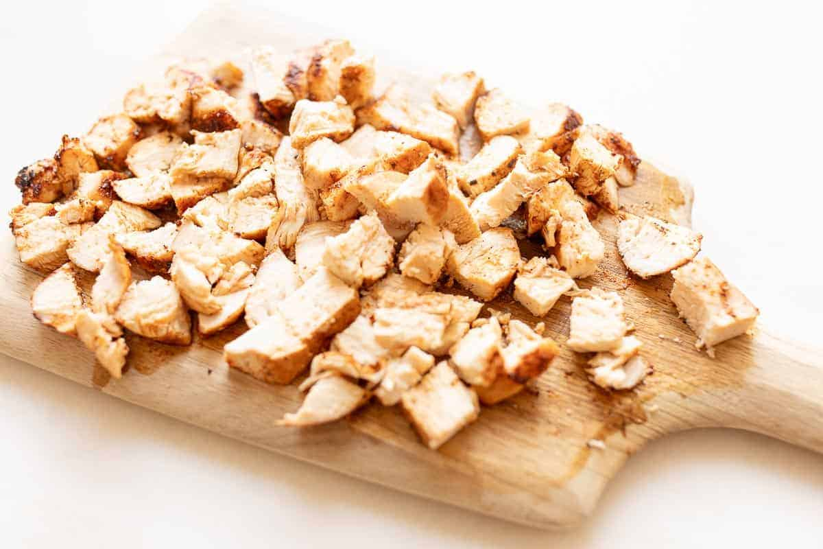 cubed chicken on wood cutting board