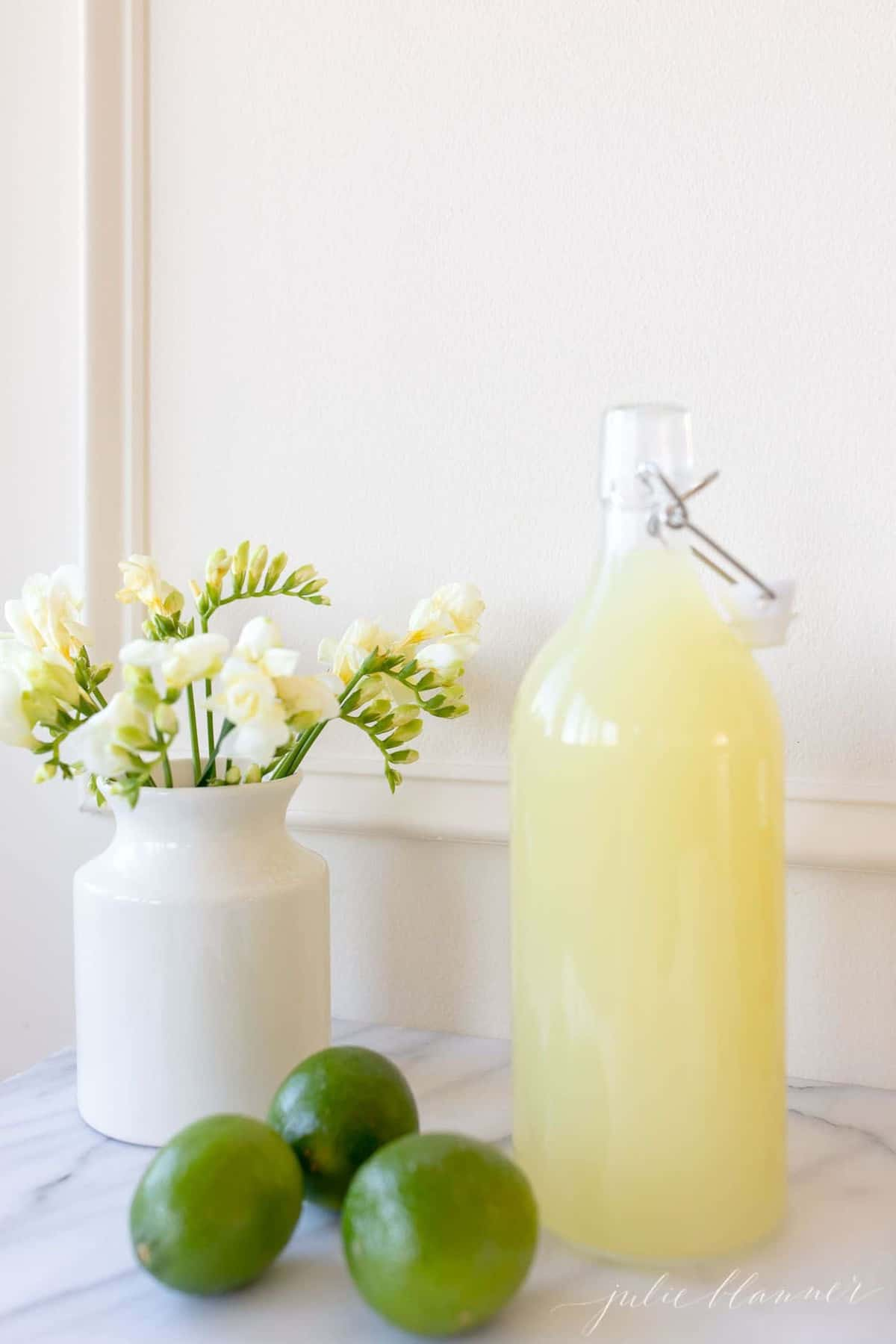 A yellow juice liquid stored in a glass carafe; a vase full of yellow flowers sits to the side.