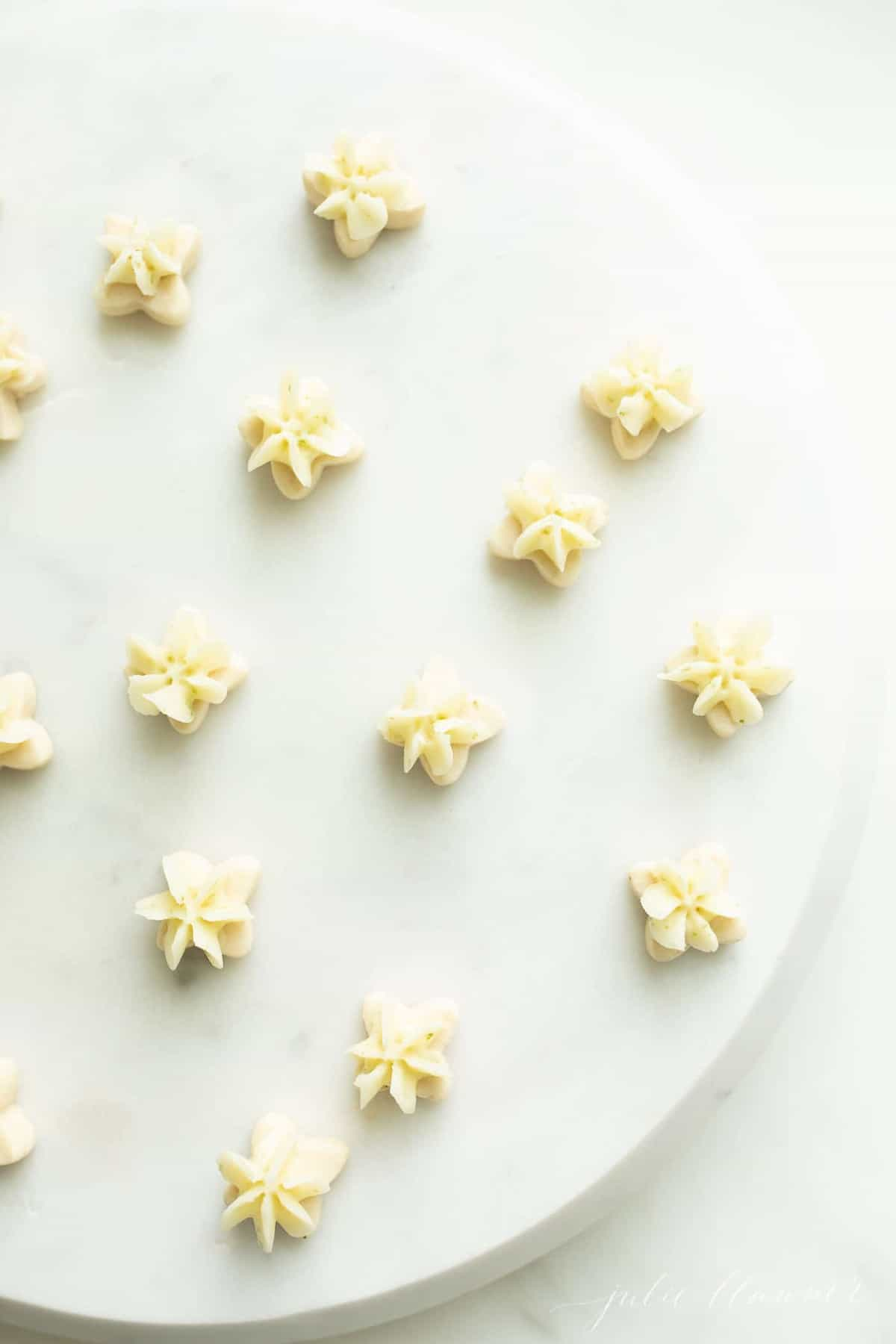 A marble surface full of tiny key lime cookies with frosting.