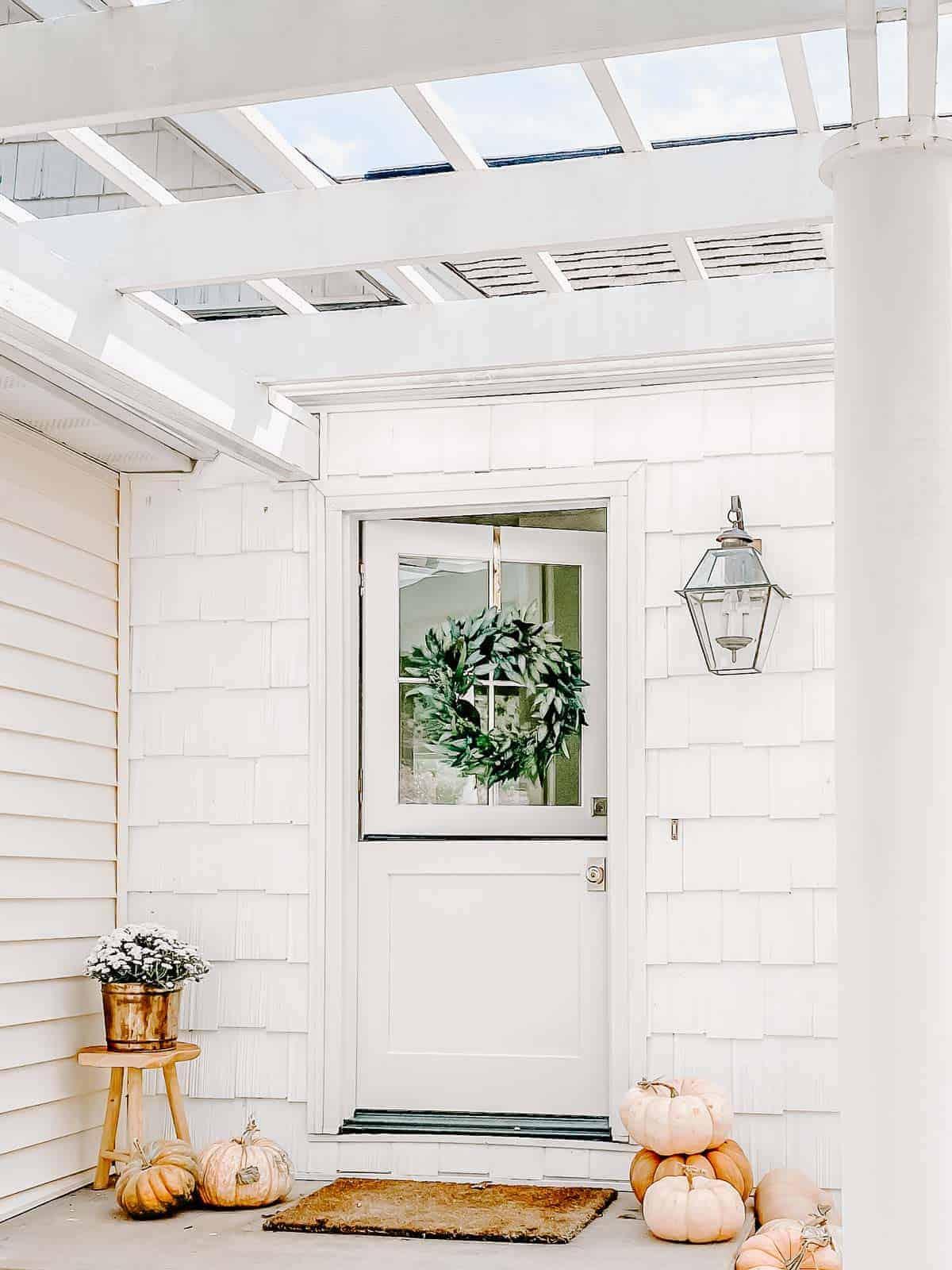 white porch with dutch door and pergola
