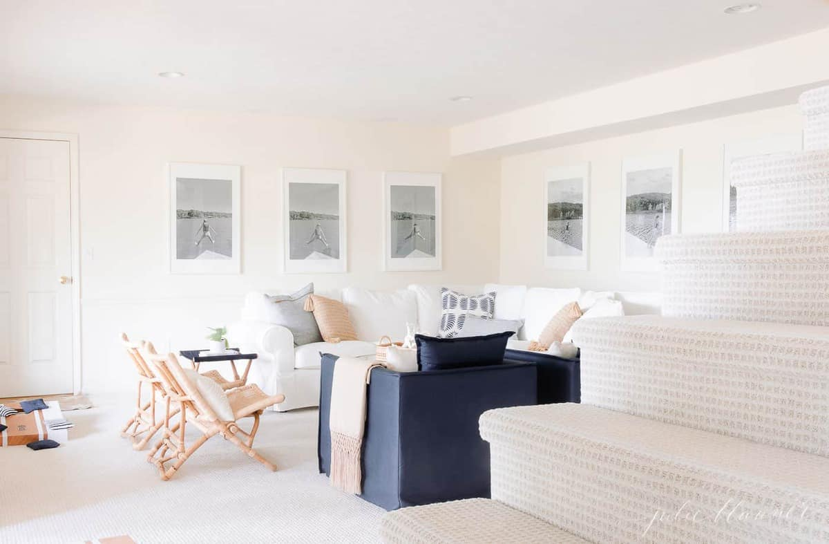lake house living room with soft cream walls and carpet navy and white furniture