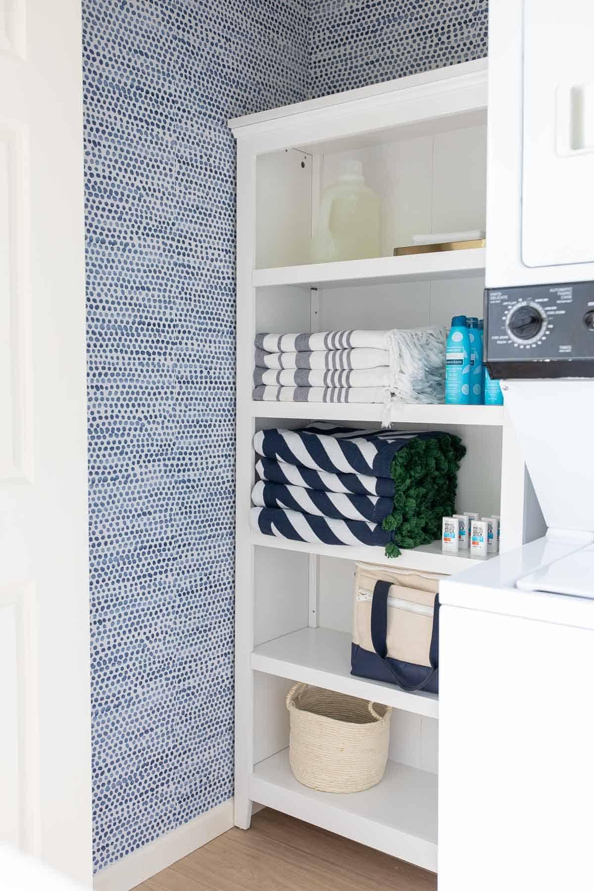 laundry closet with storage shelves