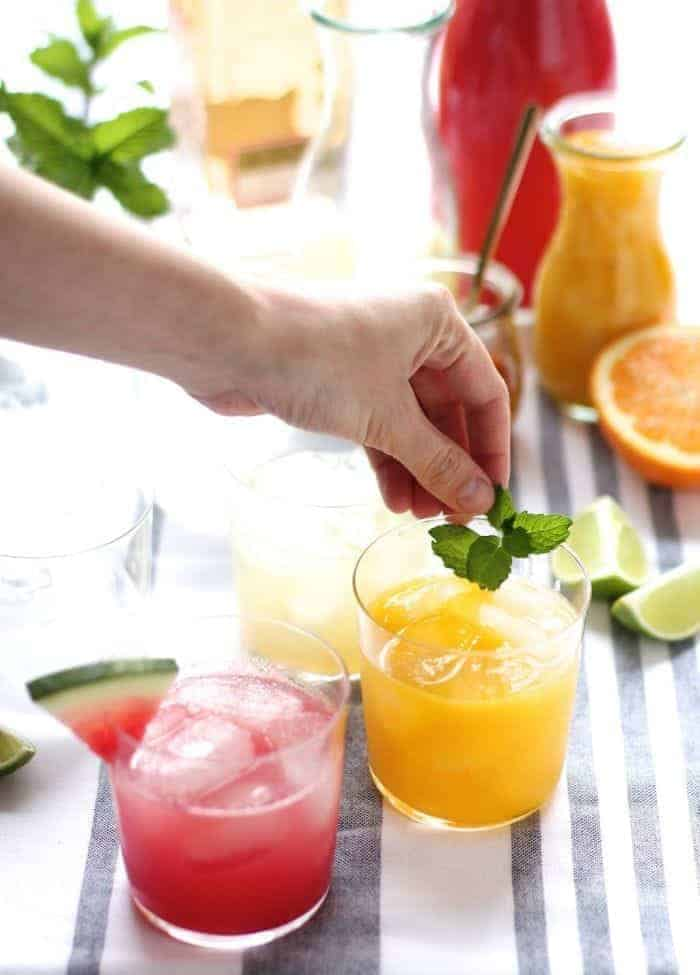 An array of margaritas and supplies in a home margarita bar, hand reaching in for garnish.