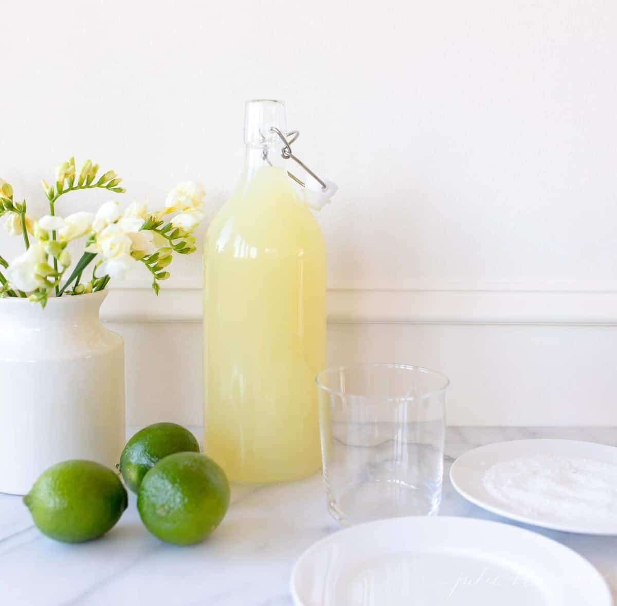 Homemade margarita mix in a glass carafe; a vase full of yellow flowers sits to the side.