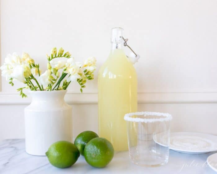 White kitchen background, glass carafe full of homemade margarita mix, limes to the side.