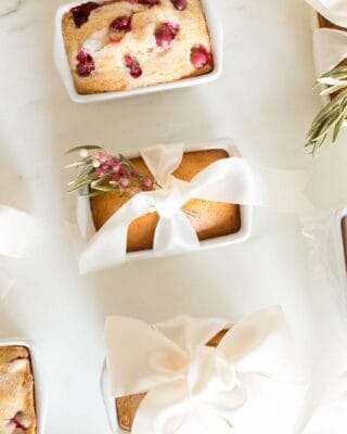 White surface with a variety of packaged mini loaves of sweet bread recipes.