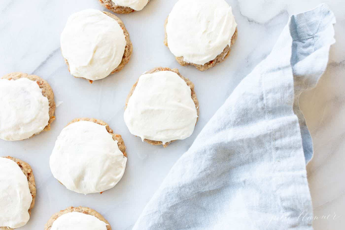 Frosted carrot cake cookies on a marble surface, blue linen towel to the side.