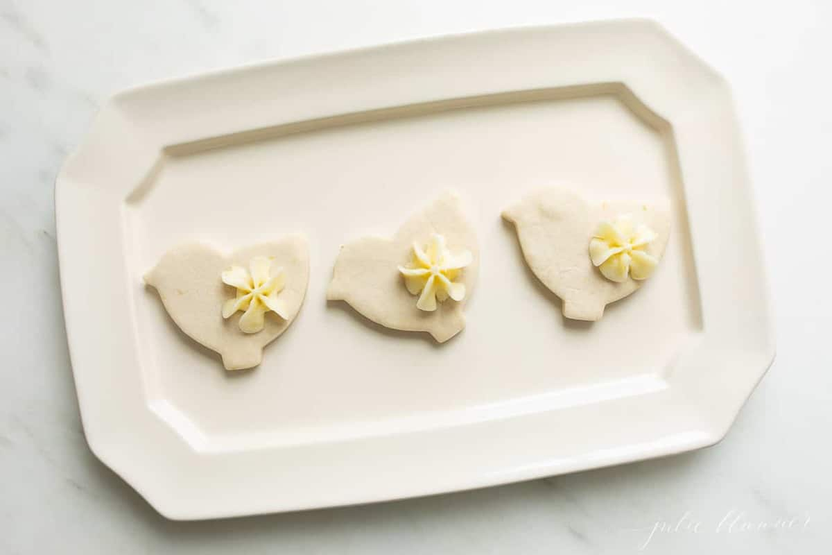 A white platter with three lemon cookies cutout as ducks.