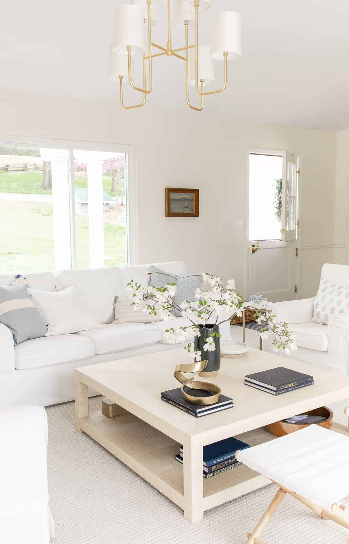 coastal style living room with white slipcovered sofas and dutch door